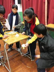 S.1 student participating in a STEM activity during the short assembly